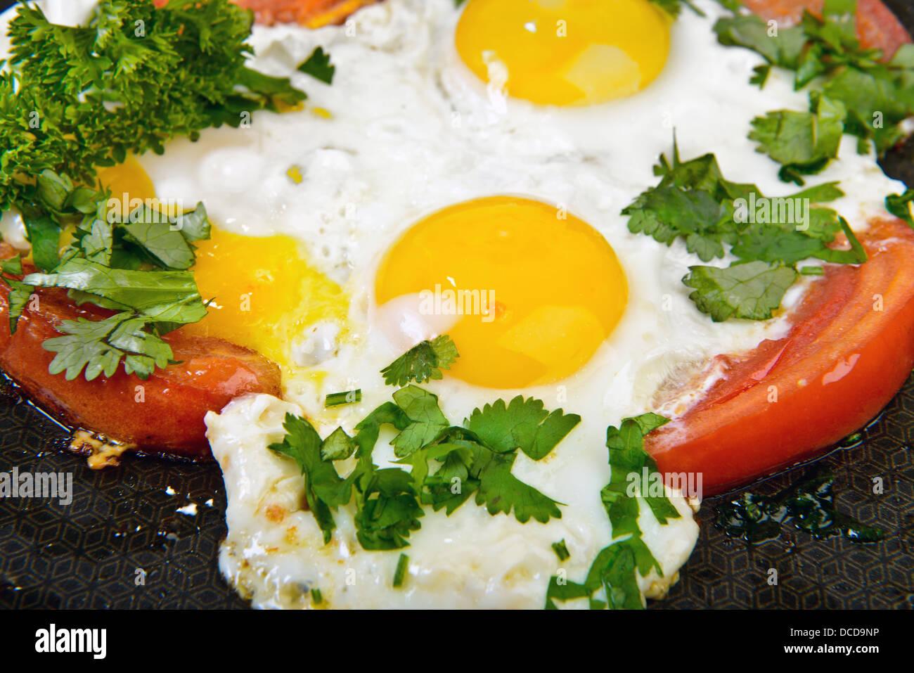 Uova fritte e il pomodoro in padella con erbe aromatiche Immagini Stock