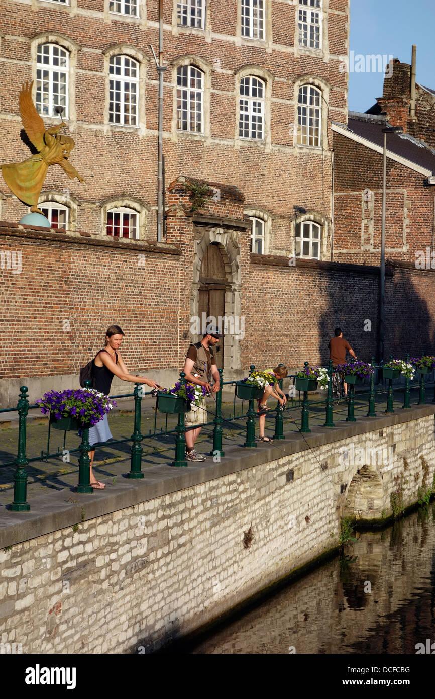 Famiglia di anlers angling in acqua di fiume Lieve lungo la Augustijnenkaai a Gand, Fiandre Orientali, Belgio Immagini Stock