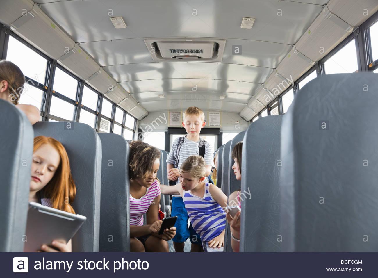 Equitazione per bambini sul bus di scuola Immagini Stock