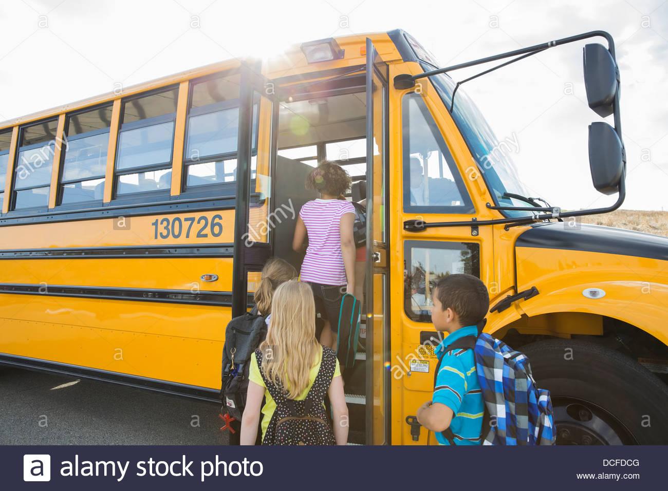 Scolari boarding school bus andando per Gita Immagini Stock