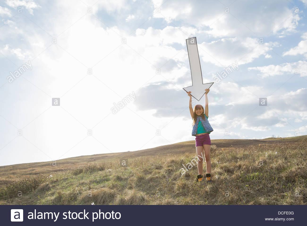 Ritratto di schoolgirl tenendo premuto verso il basso la freccia sulla collina Immagini Stock