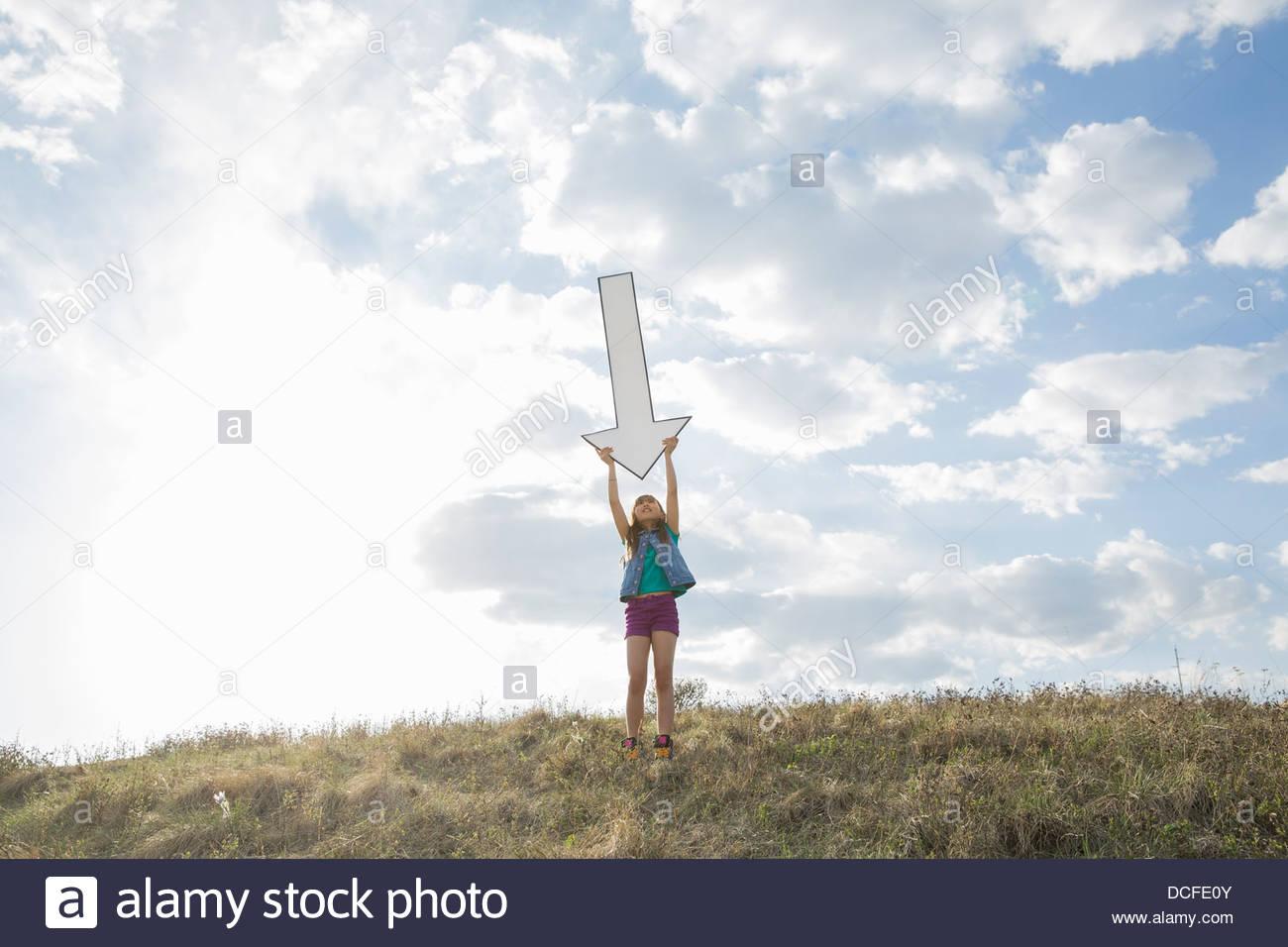 Schoolgirl tenendo premuto verso il basso la freccia sulla collina Immagini Stock