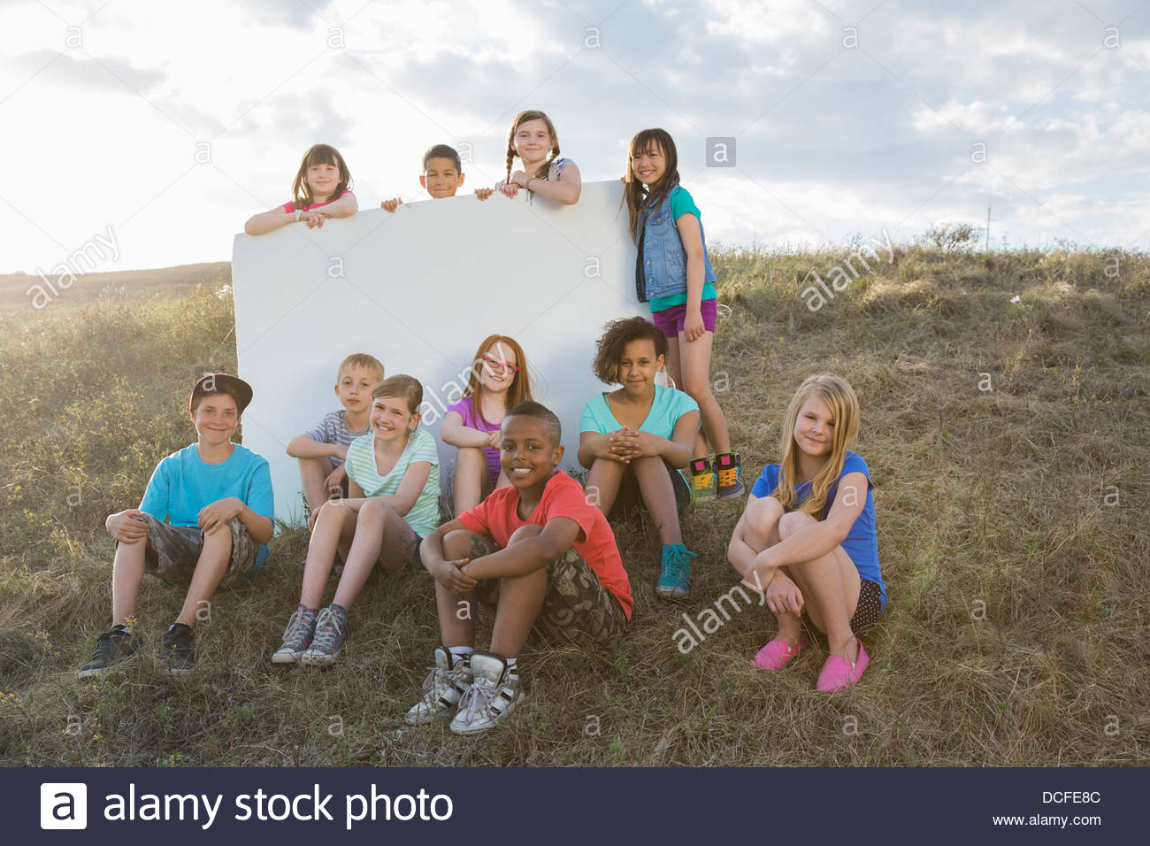 Ritratto di scolari con vuoto affissioni su pendio Immagini Stock