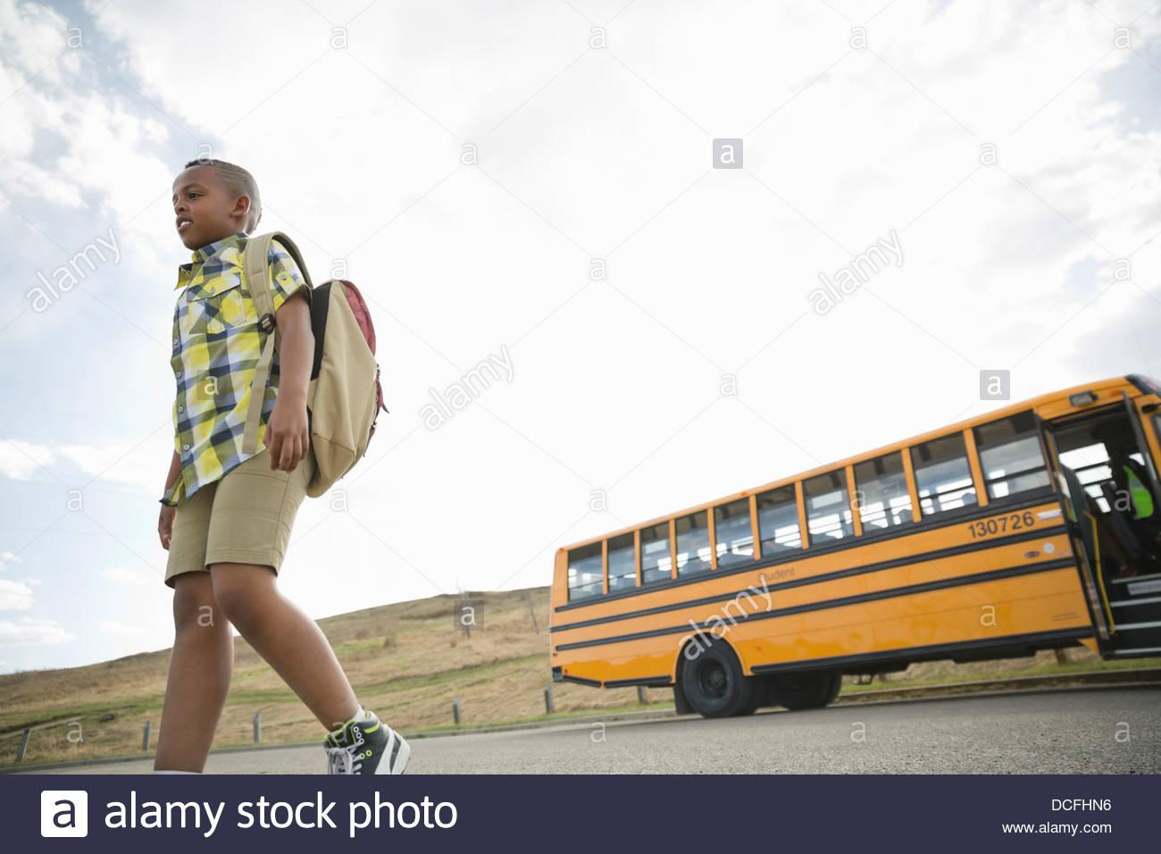 Basso angolo vista di scolaro a piedi dalla scuola bus Immagini Stock