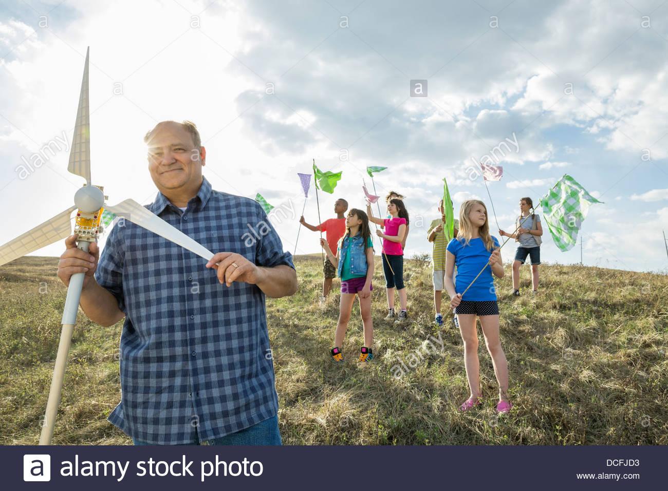 Insegnante che mostra ai bambini come una turbina eolica modello funziona all'aperto Immagini Stock