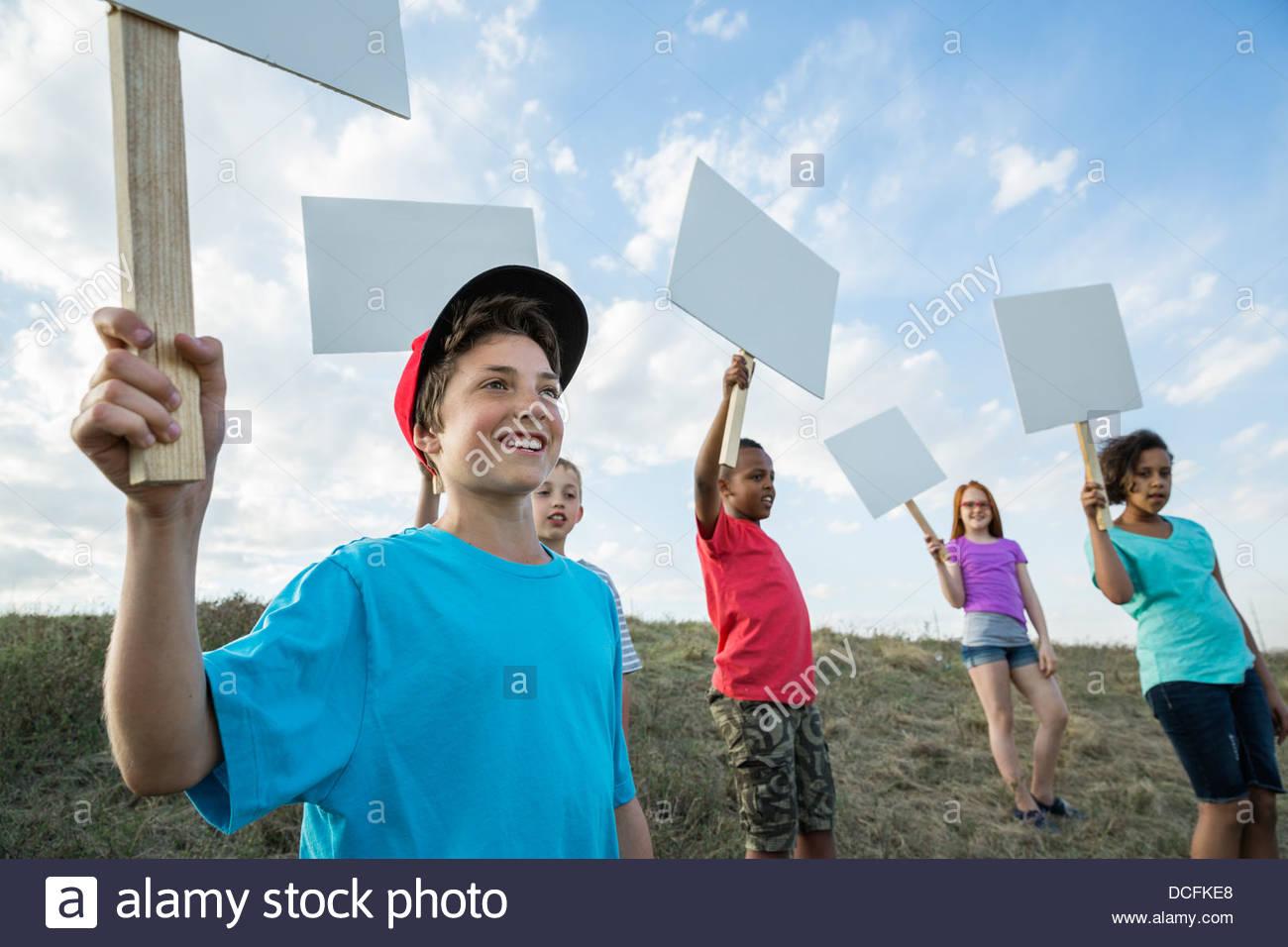 Ragazzo sorridente holding vuoto segno bordo su pendio Immagini Stock