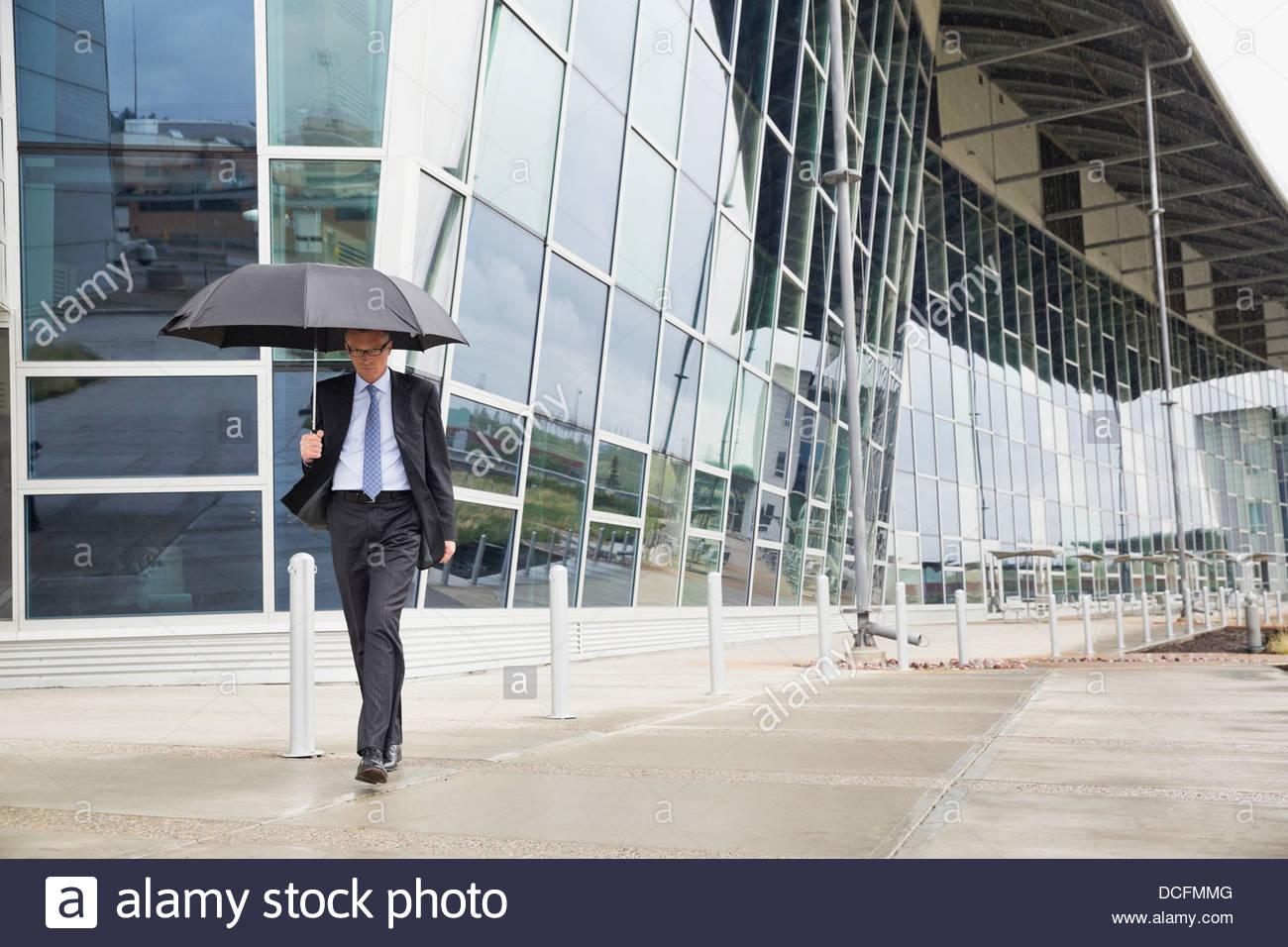Imprenditore a piedi con ombrellone Immagini Stock