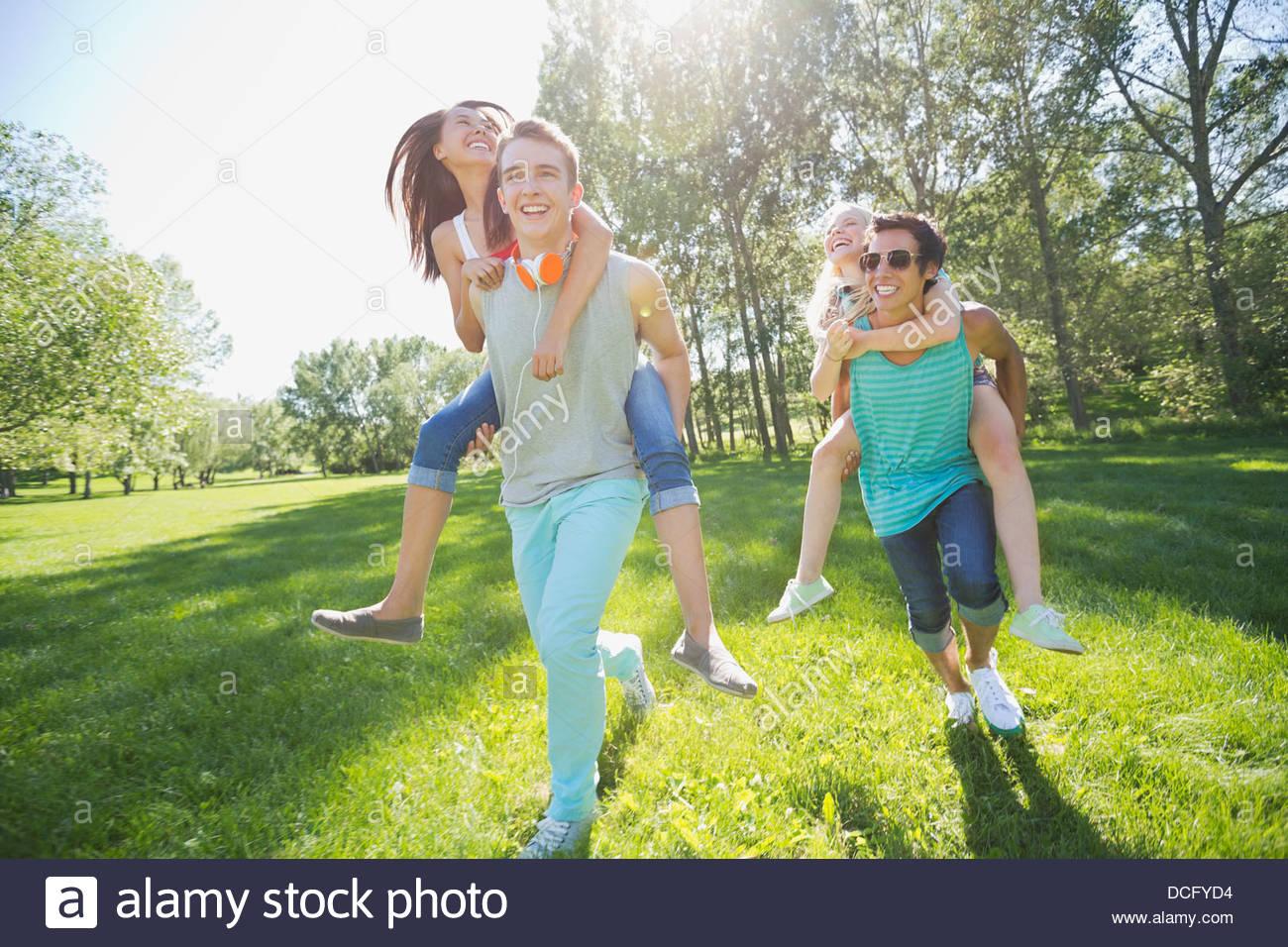Gli adolescenti dando piggyback rides Immagini Stock