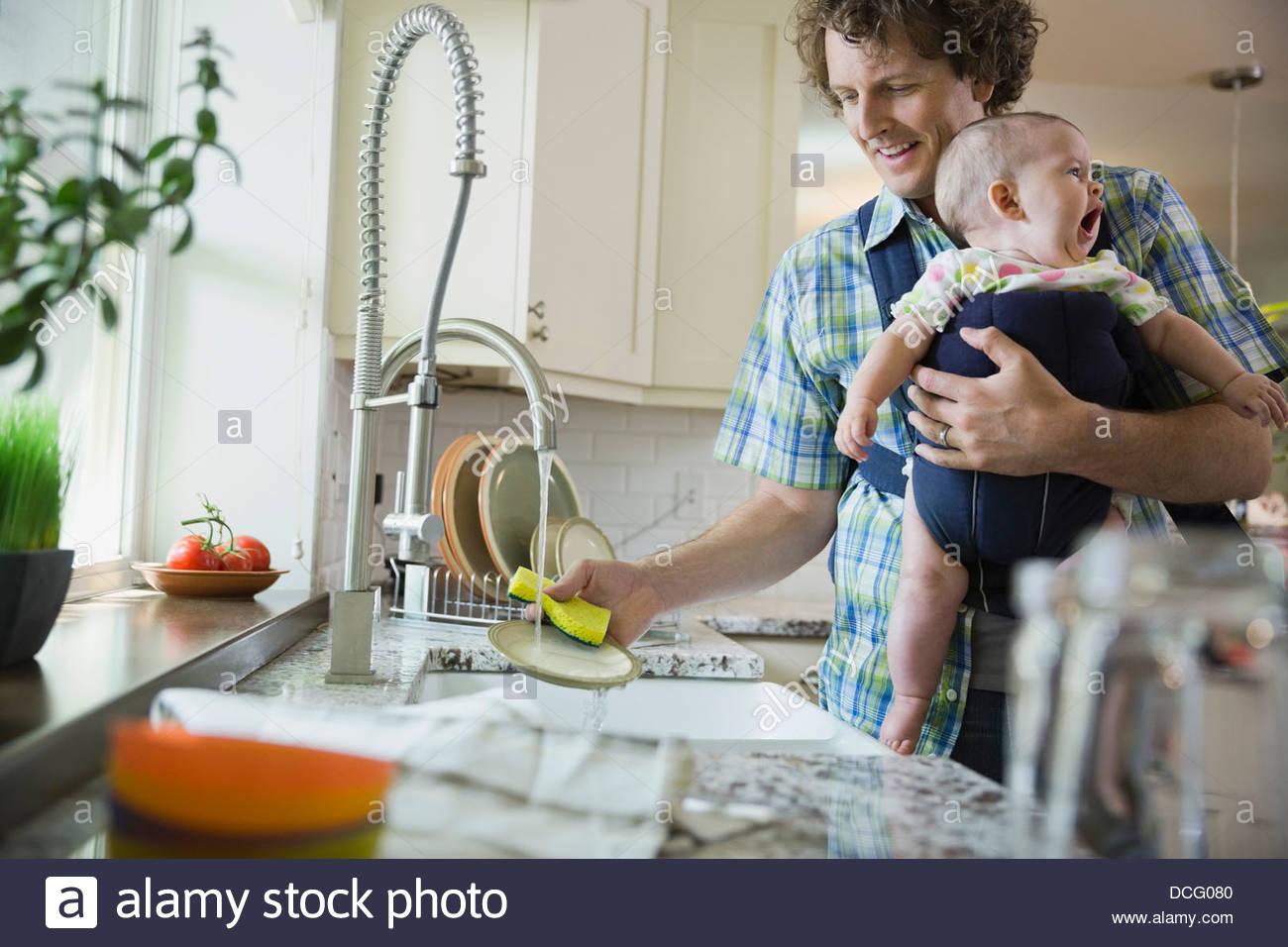 Padre lavaggio piatti mentre trasportano Baby girl Immagini Stock
