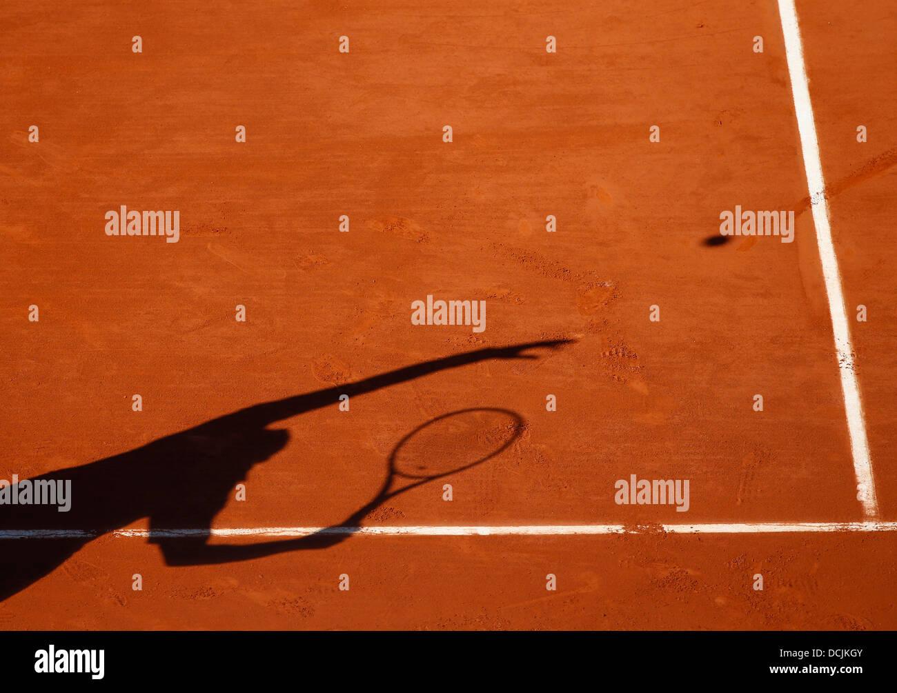 Ombra di un giocatore di tennis che serve la sfera. Immagini Stock