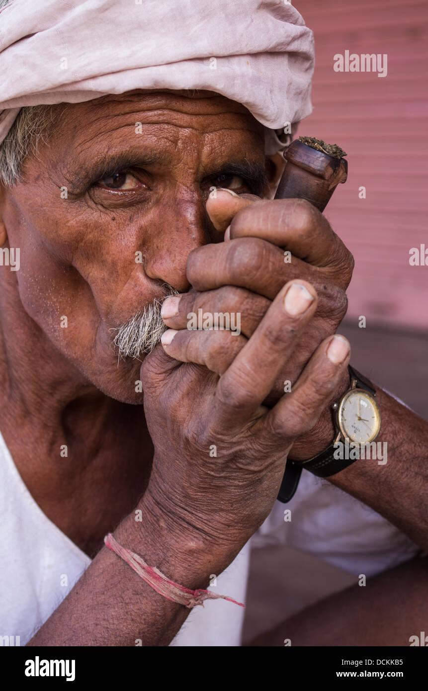 Uomo indiano di tabacco da fumo con tubazione - Jaipur, Rajasthan, India Immagini Stock