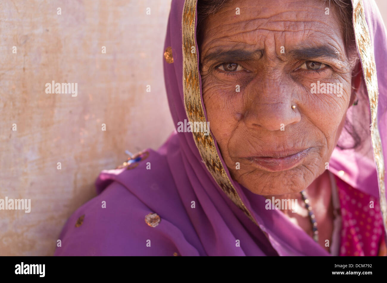 Anziani donna indiana in viola sari all'Amber ( Amer ) Fort / Palace - Jaipur, Rajasthan, India Immagini Stock