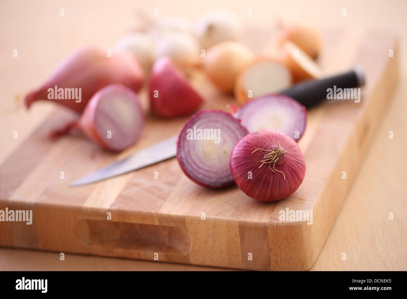 Assortimento di Cipolle e scalogni sul bordo di taglio Foto Stock