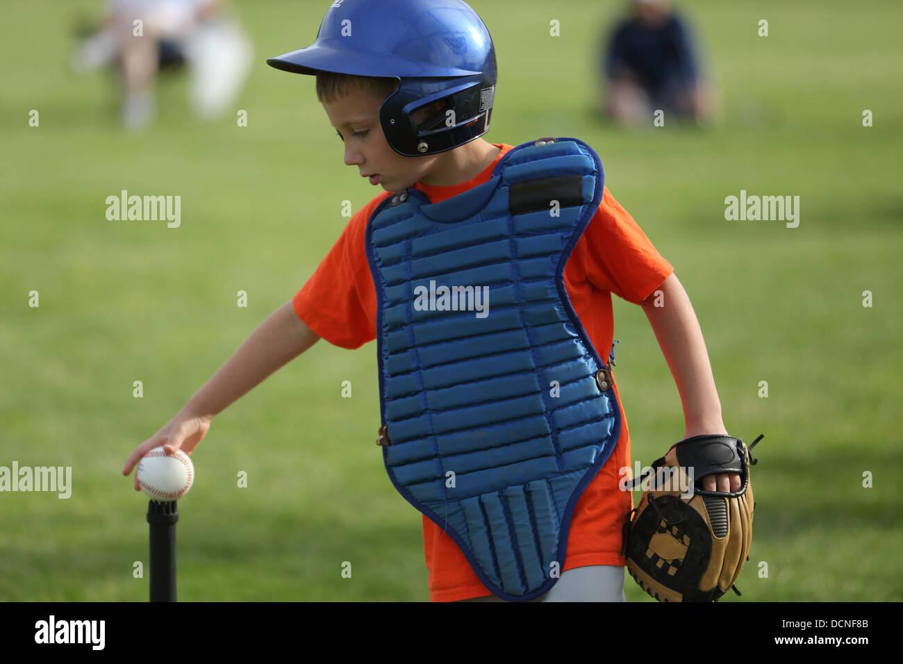 Ragazzo giovane mette a baseball sul raccordo a T Immagini Stock