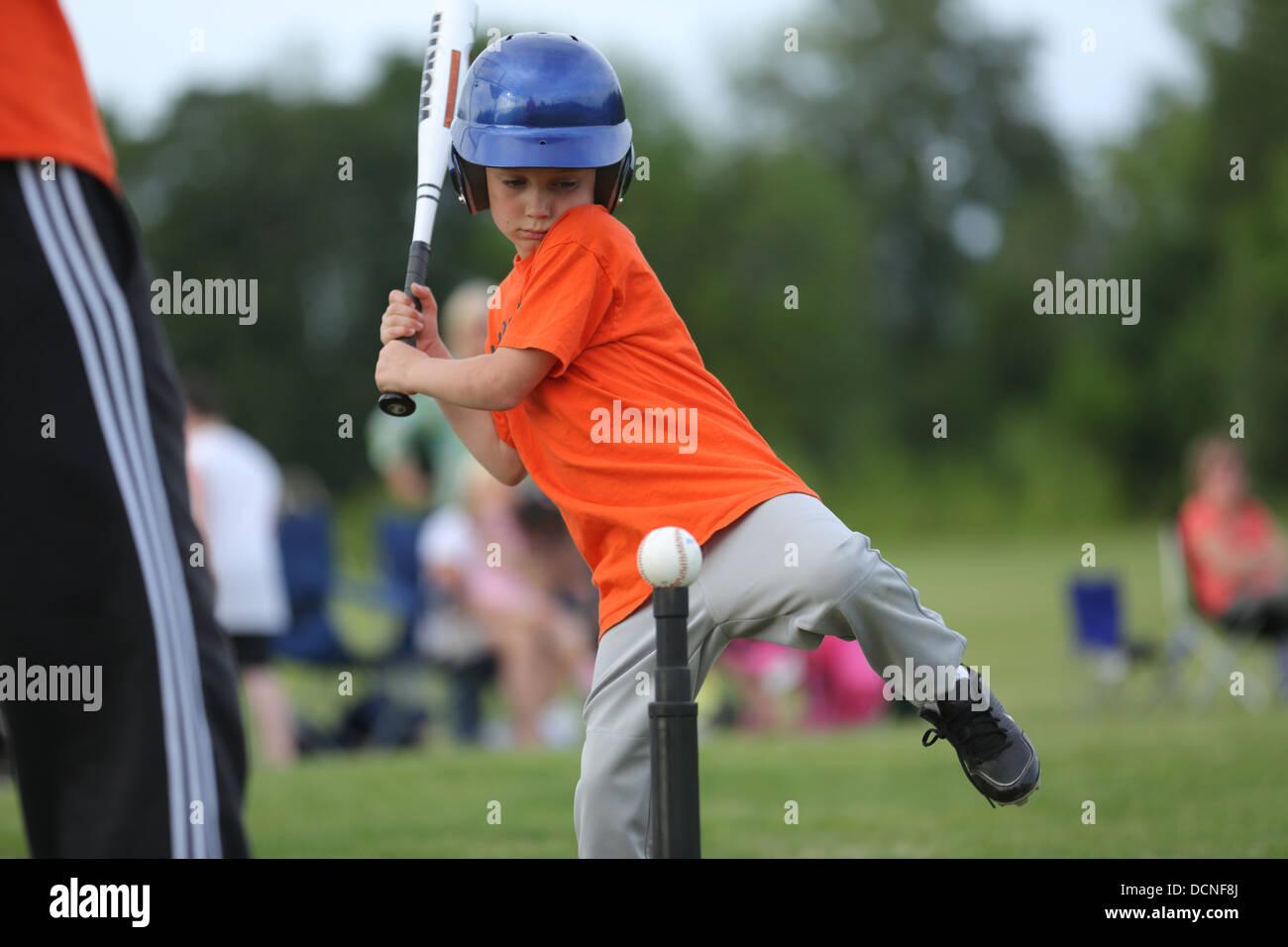 Ragazzo giovane colpendo t-ball Foto Stock