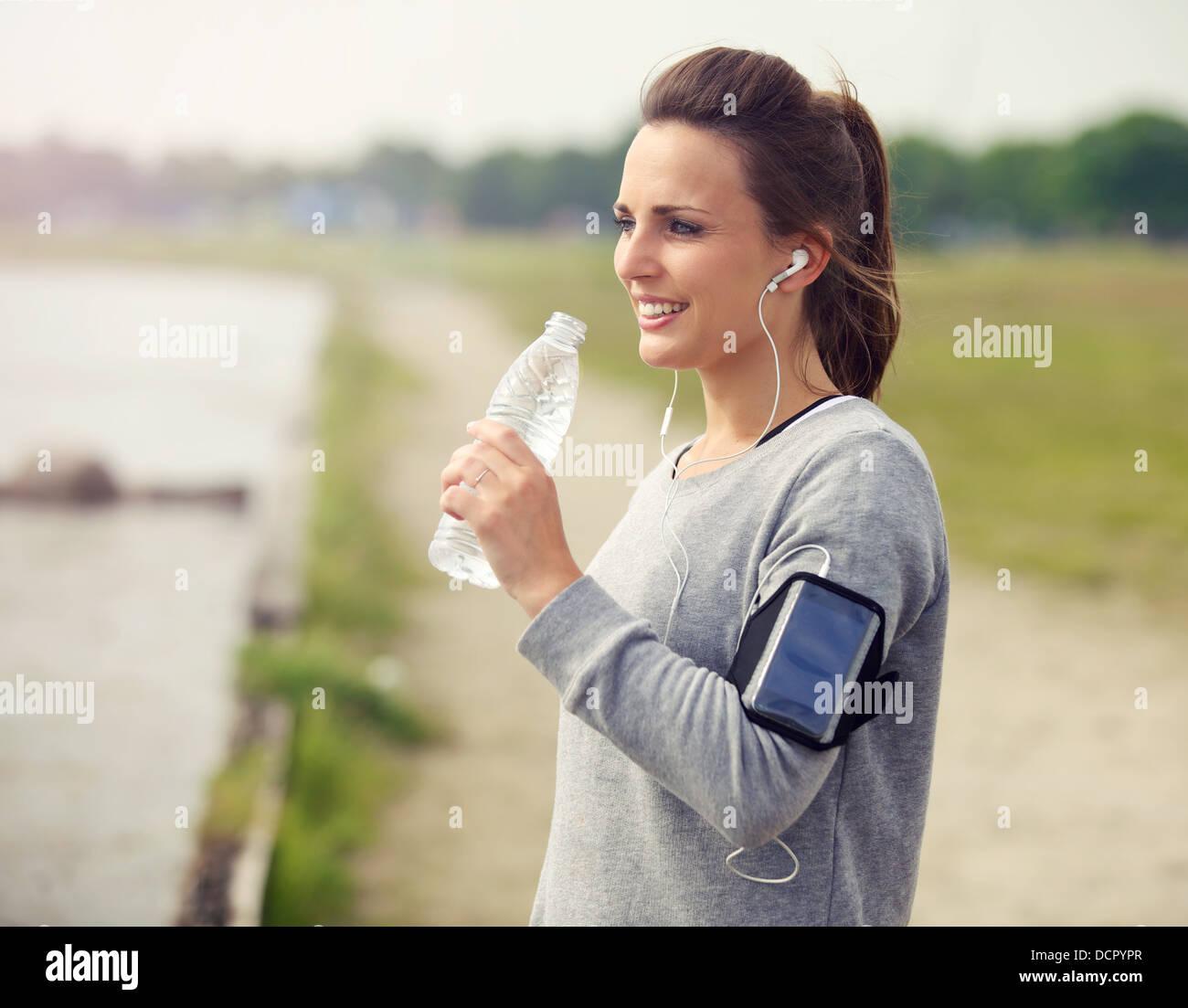 Donna sorridente runner mentre si beve acqua in bottiglia Immagini Stock