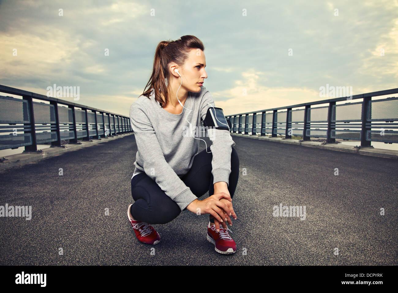 Femmina runner fitness seduto da solo sul ponte di appoggio Immagini Stock