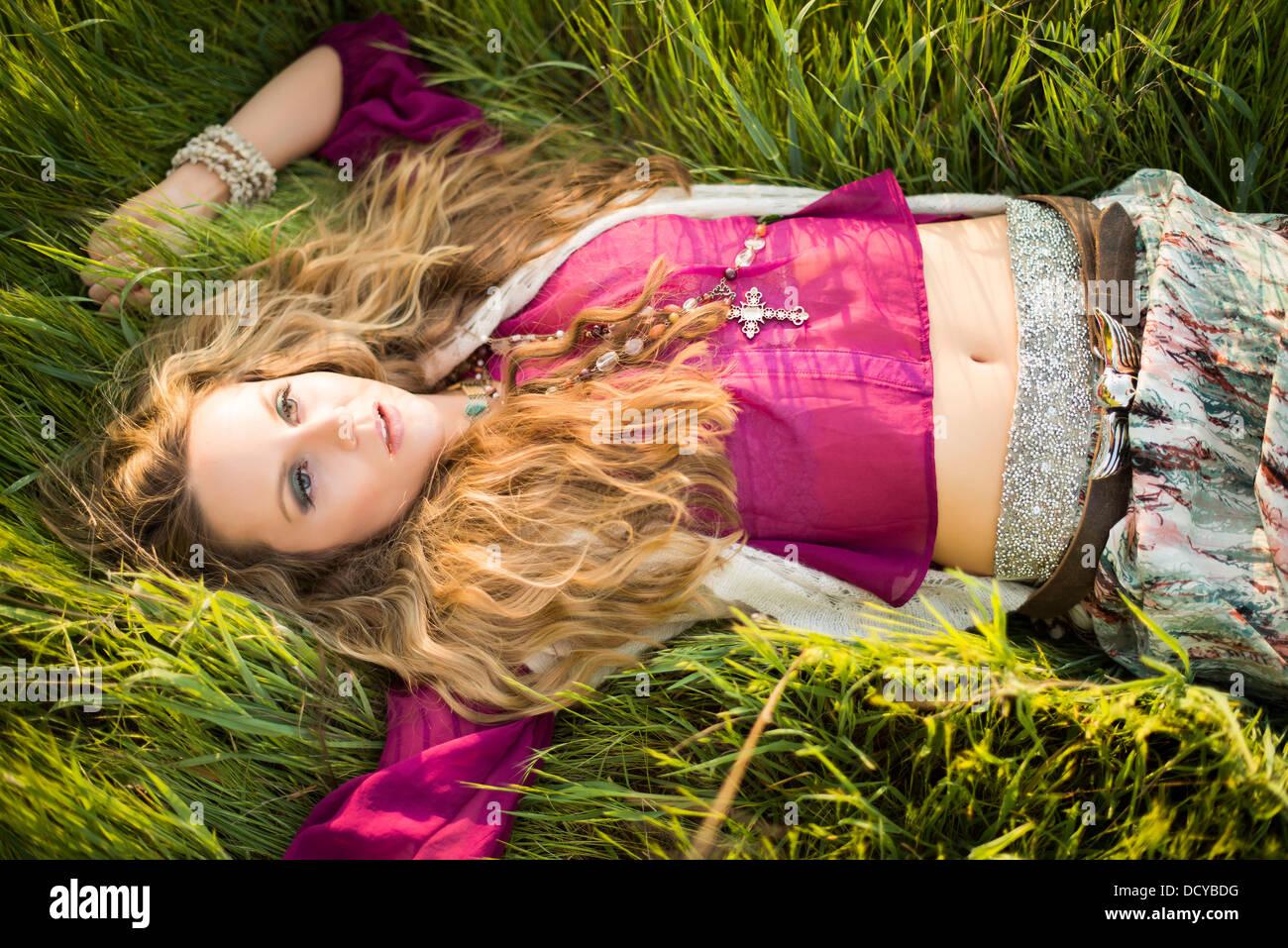 Donna sdraiata in erba lunga Foto Stock