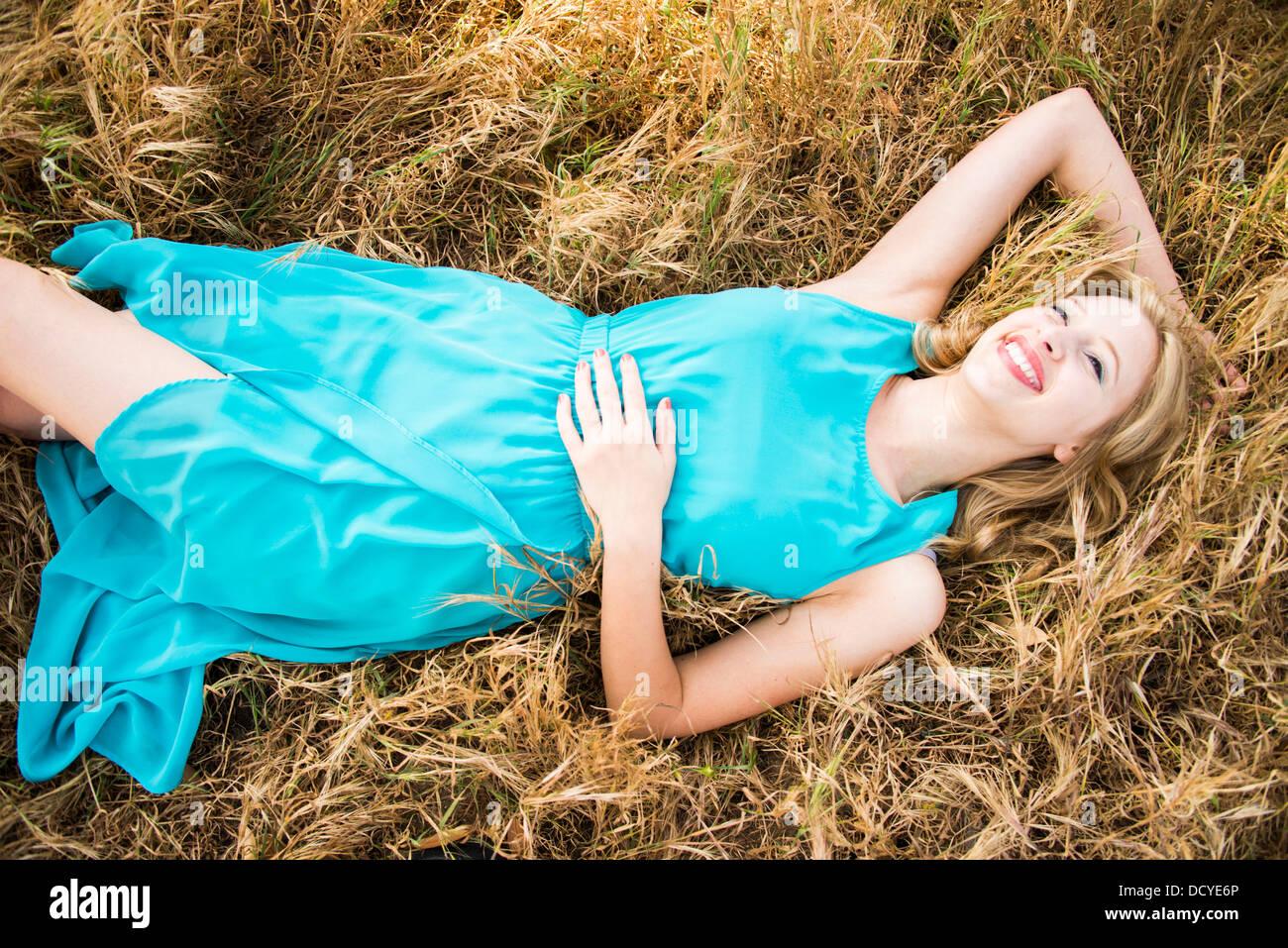 Donna sorridente giacente in erba Foto Stock