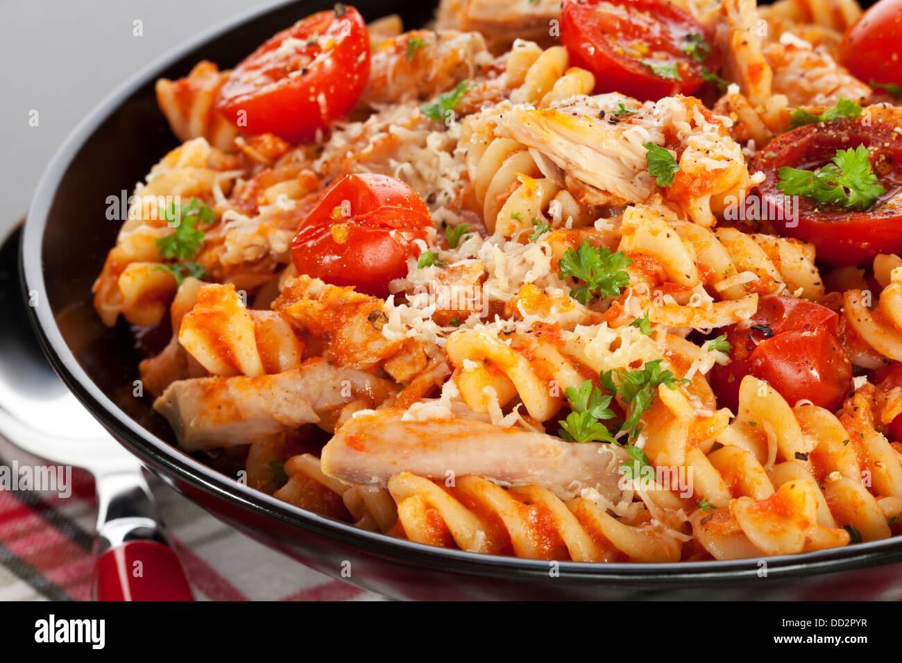 Cuocere la pasta con tonno e pomodori ciliegia - un individuo che serve di cuocere la pasta con pomodorini e tonno Immagini Stock