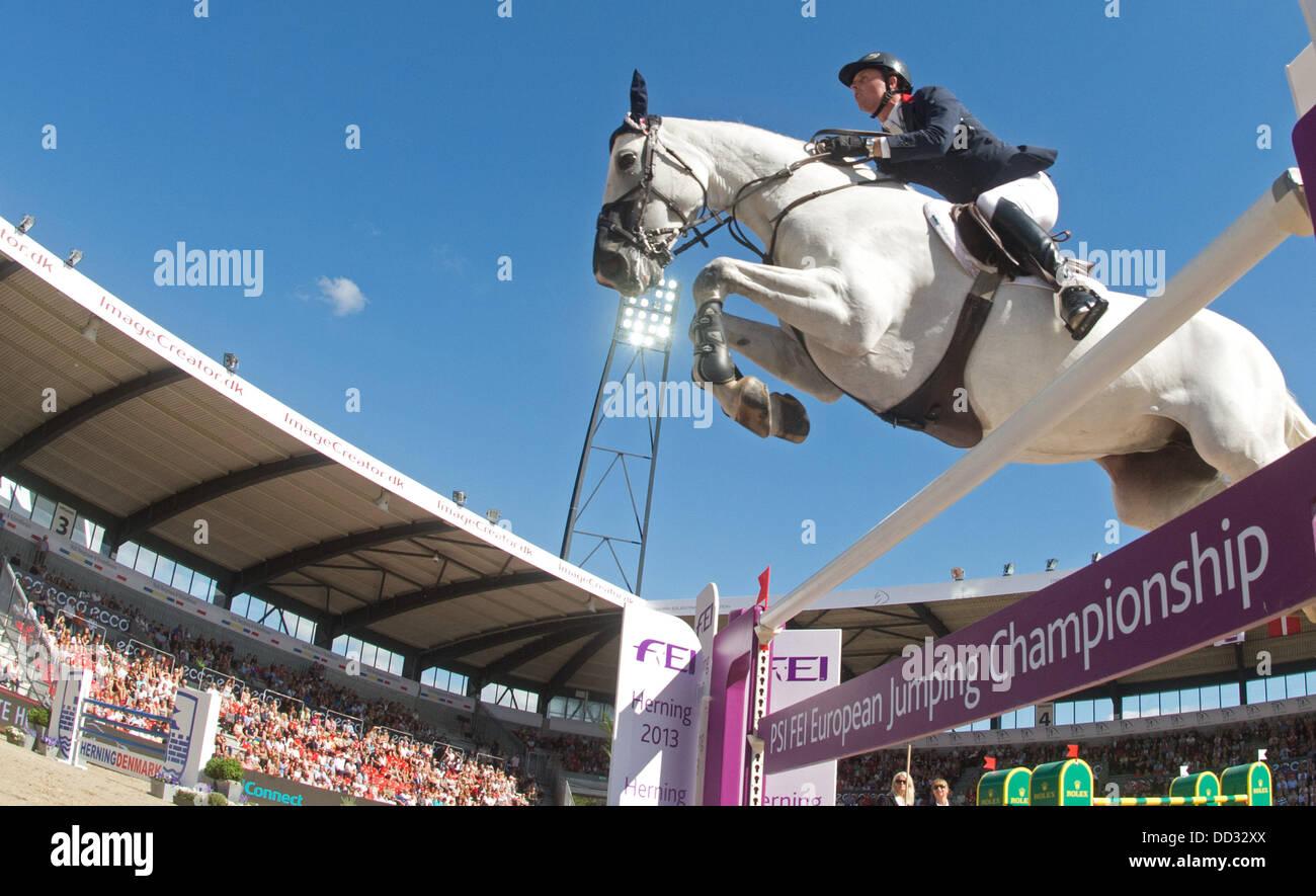 Herning, Danimarca. 24 Ago, 2013. British mostra il ponticello Ben Maher salta sopra un ostacolo sul suo cavallo Immagini Stock