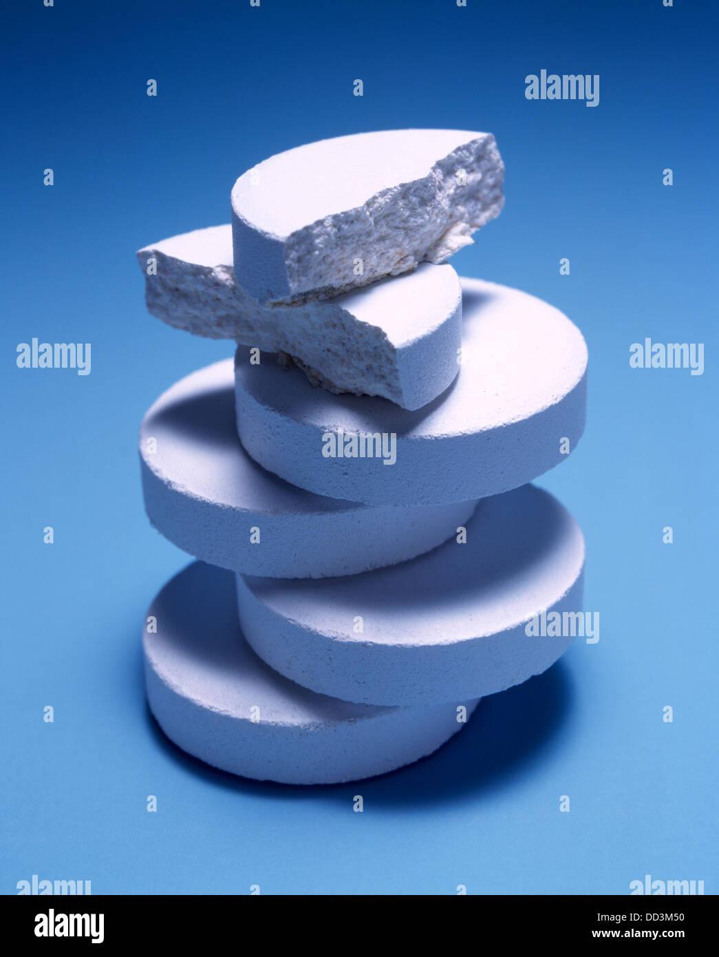 Una grande pila di medicina bianco compresse su uno sfondo blu. Immagini Stock