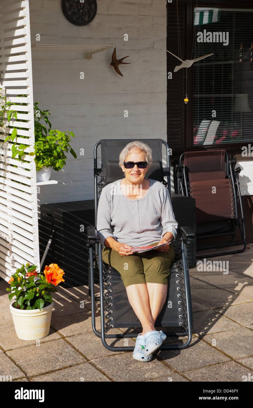 Donna nella sua 70s nel suo giardino lettura di riviste felice sul giorno di estate Finlandia occidentale nord europa Immagini Stock