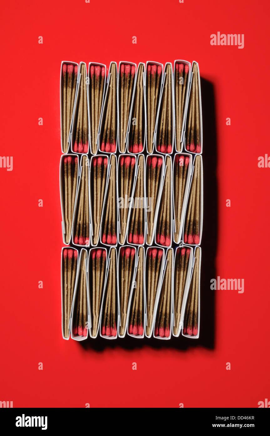 Confezioni di corrispondenze fra di loro per formare un unico modello. Forma rettangolare, sfondo rosso Immagini Stock