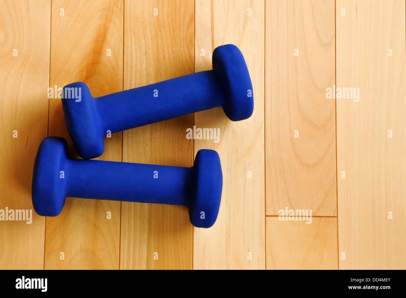 Pesi blu sul pavimento di legno duro di Centro Fitness, vista da sopra, spazio di copia Immagini Stock
