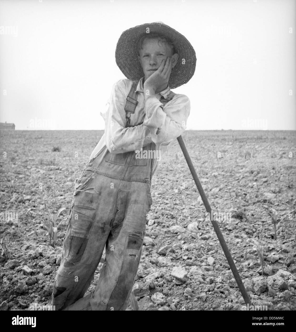 Poveri bianchi farm boy appoggiata sulla sua zappa nella Carolina del Nord. Luglio 1936. Fotografia di Dorothea Foto Stock