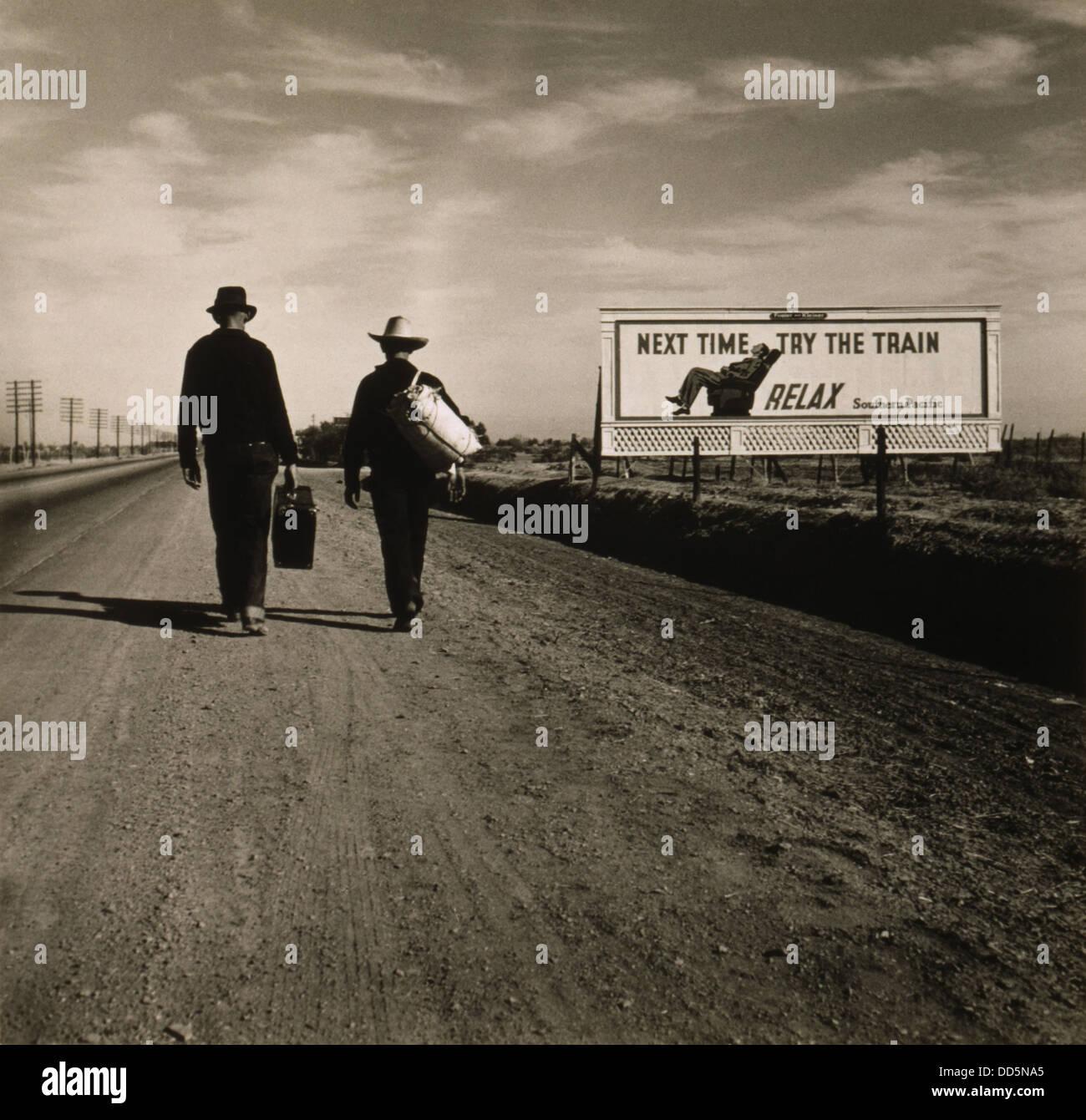 Due uomini in cammino verso Los Angeles, marzo 1937. Davanti a loro è un Southern Pacific Railroad lettura Immagini Stock
