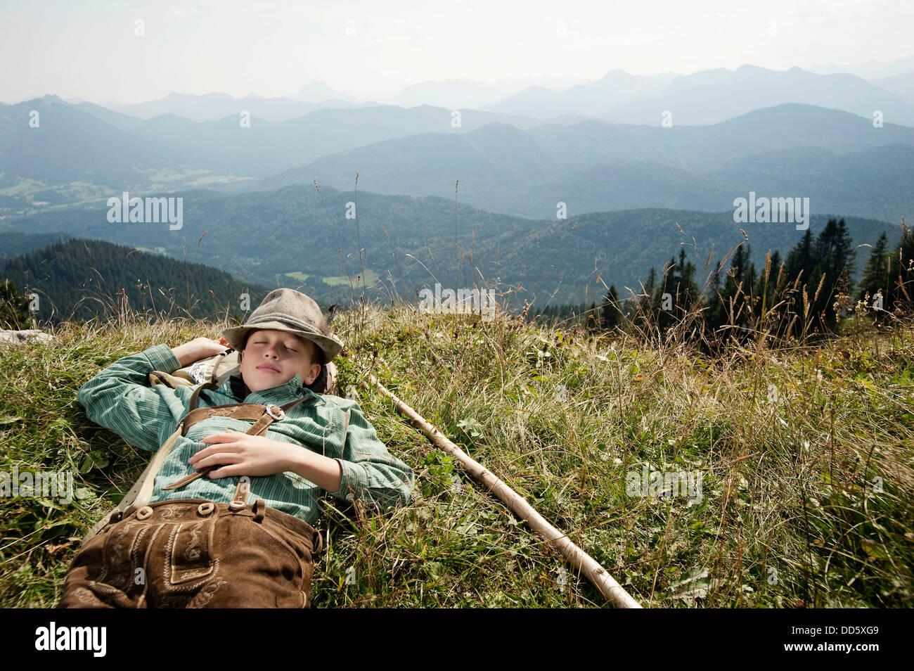 In Germania, in Baviera, ragazzo in abiti tradizionali dorme in montagna Immagini Stock
