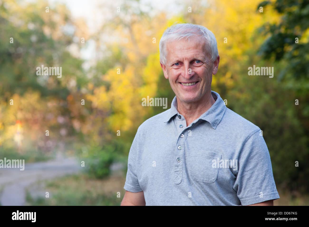 Ritratto di felice volto sorridente di grigio con capelli uomo vecchio.  All esterno. Jeans blu. Grigio t-shirt. 5a3ad7ac18ec