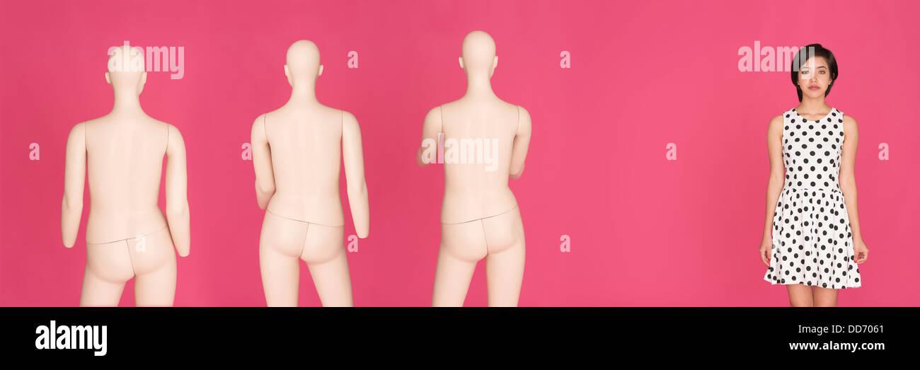 Ritratto concettuale di giovani gravi multirazziale donna in piedi da soli, lasciato fuori da un gruppo di manichini Immagini Stock