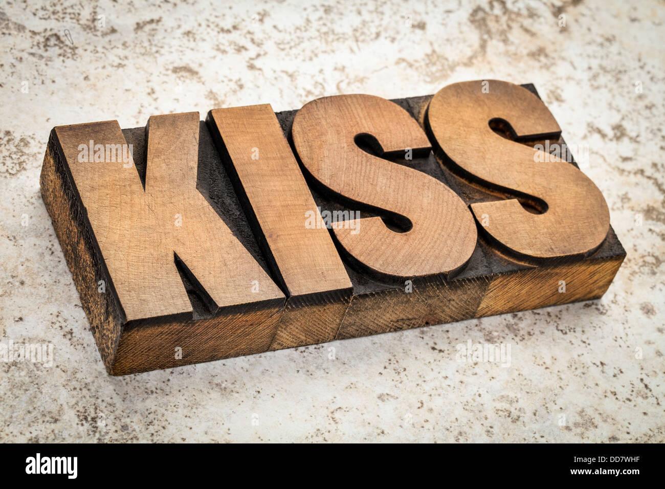 Kiss parola o acronimo (keep it simple stupid) in rilievografia tipo di legno contro la piastrella ceramica Immagini Stock