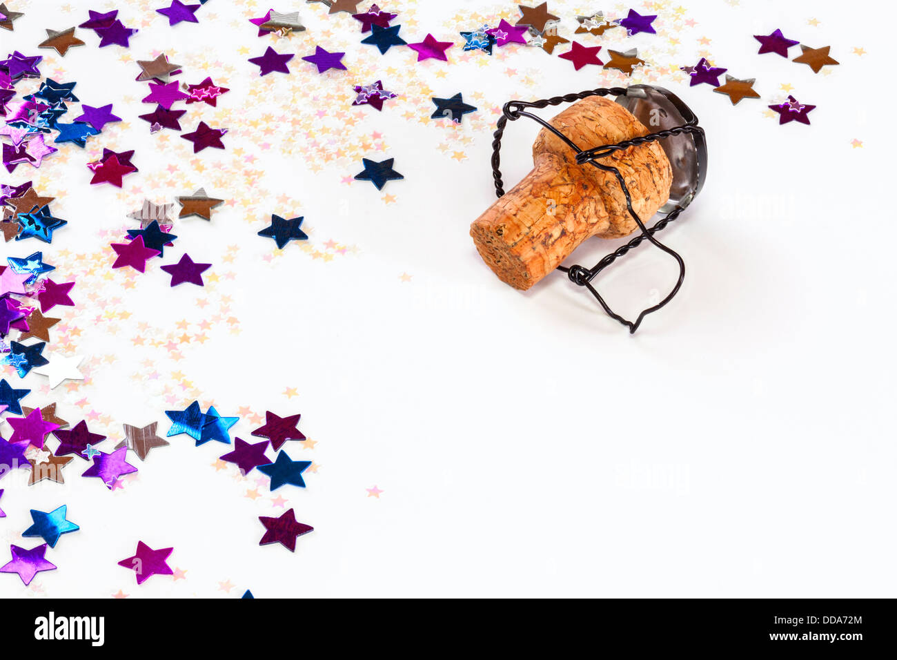 Tappo dello Champagne e coriandoli - champagne con i confetti o glitter su sfondo bianco con copia spazio. Immagini Stock