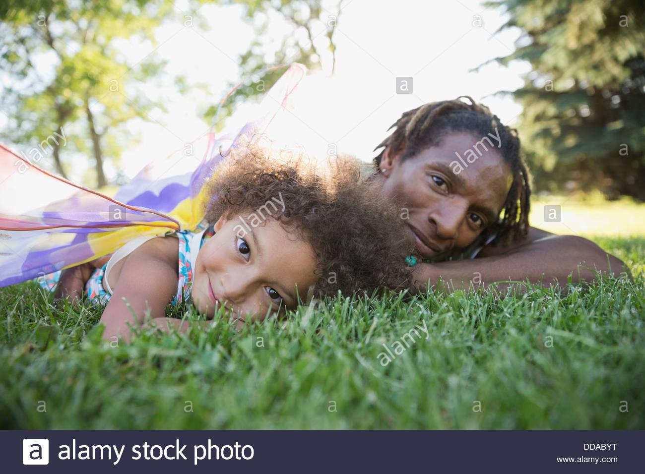 Padre e figlia giacente sull'erba Immagini Stock