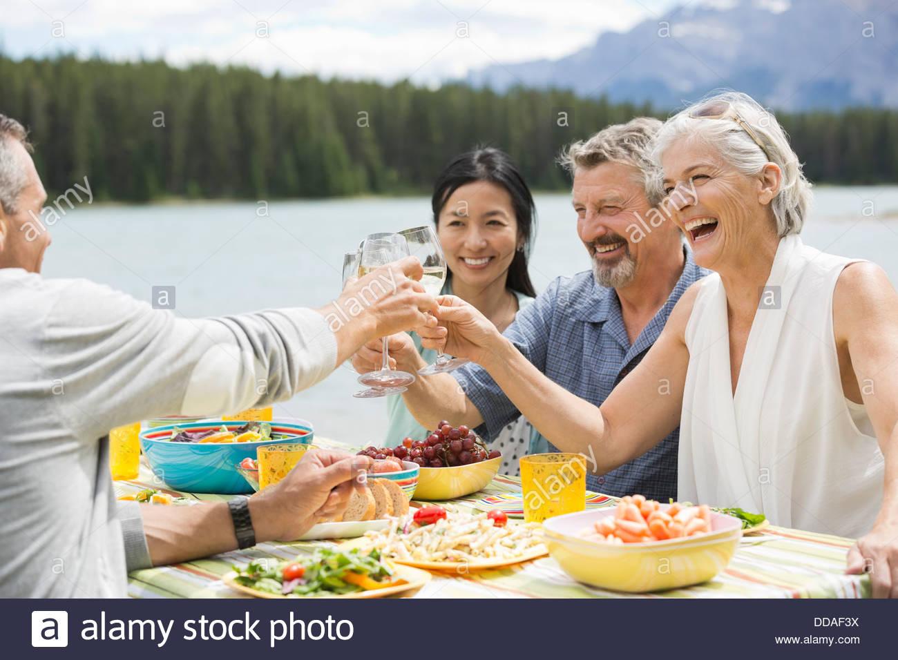 Allegro amici bevande di tostatura a un picnic esterno Immagini Stock
