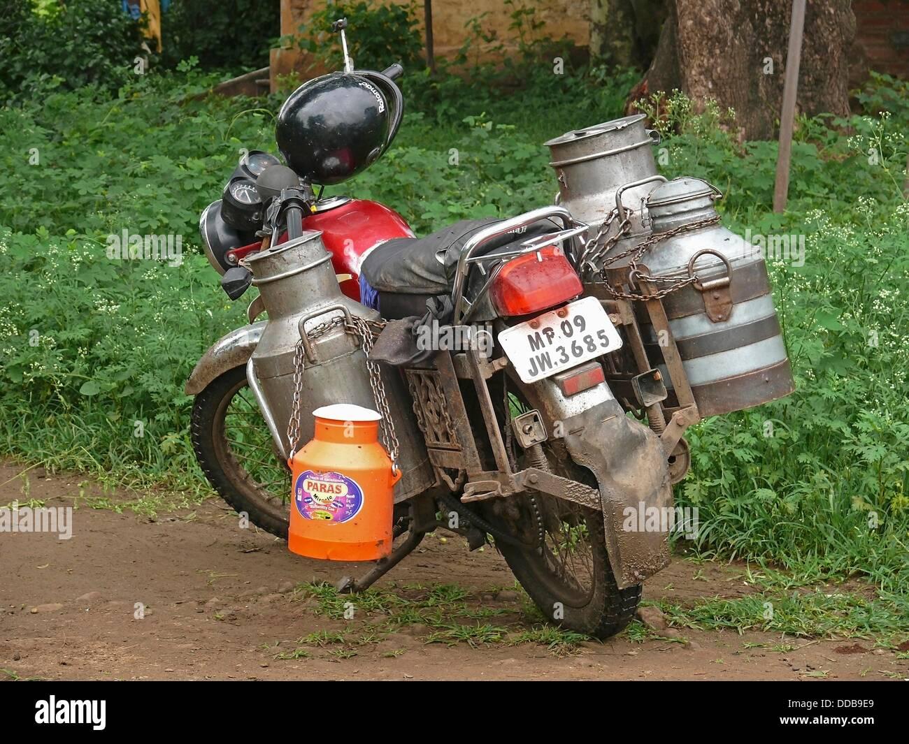 Motocicletta con vettori di latte per la consegna, Maharashtra, India Immagini Stock