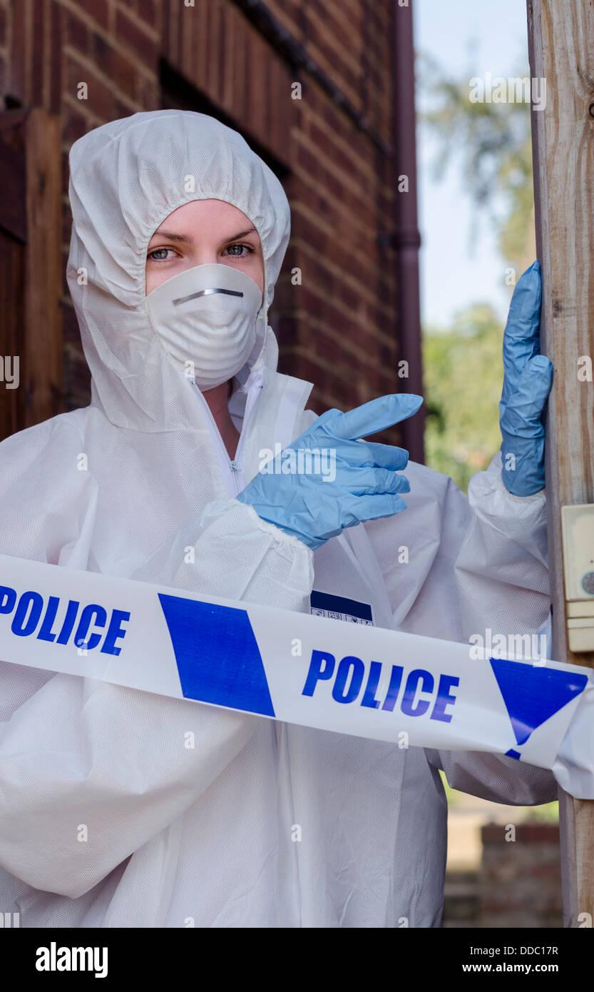 Investigatore della scena del crimine dietro un cordone di polizia Immagini Stock