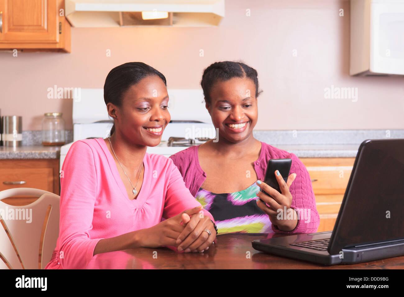 Due suore che lavorano con lo smartphone e il computer portatile a casa, uno con disabilità di apprendimento Immagini Stock