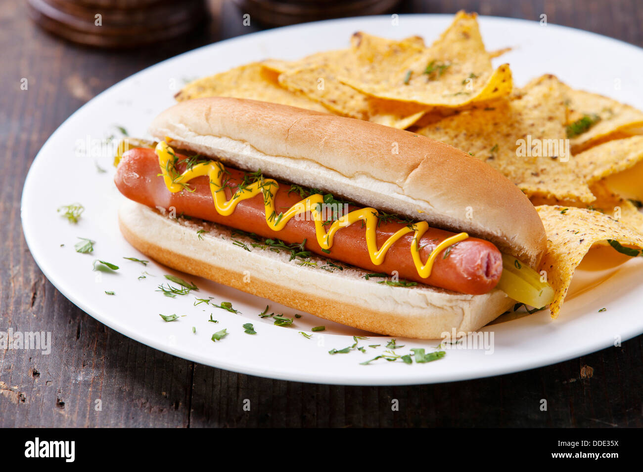 Hot Dog con senape e patatine su sfondo di legno Immagini Stock