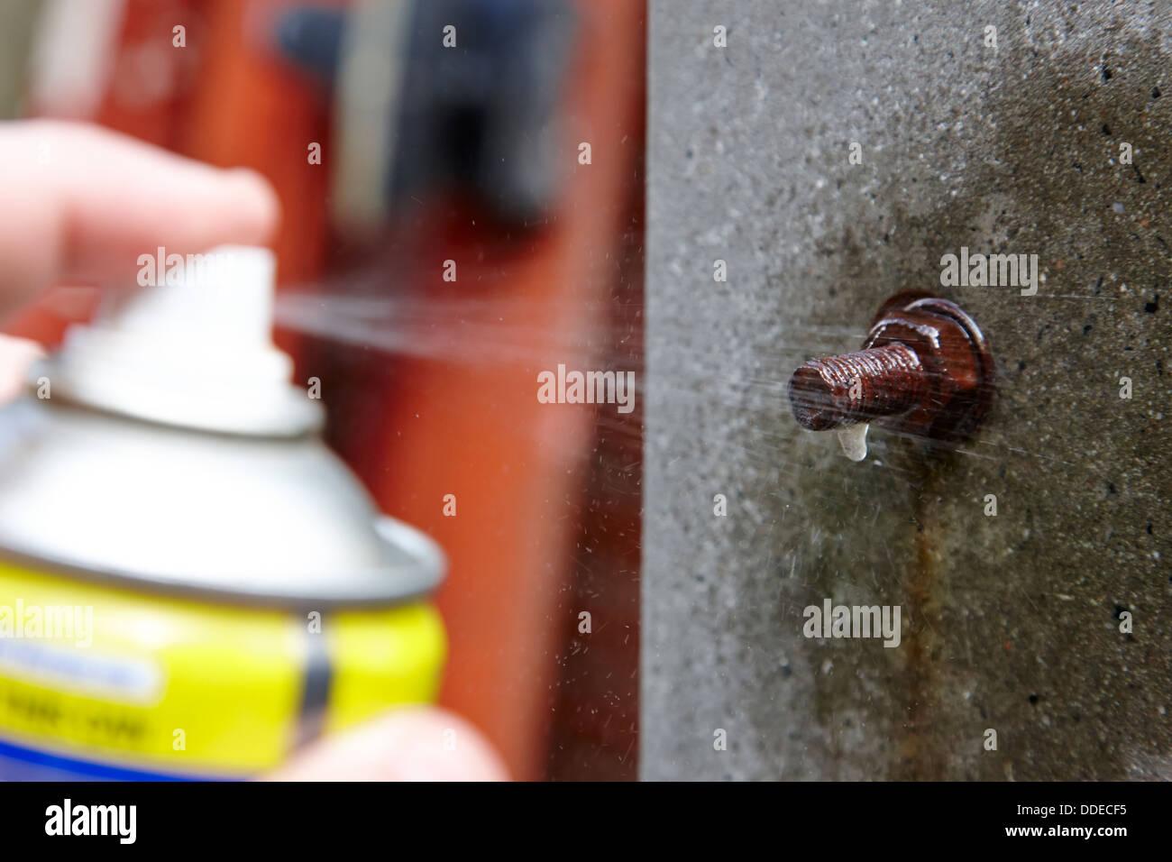 L'uomo la spruzzatura di bullone arrugginito con liquido penetrante Immagini Stock
