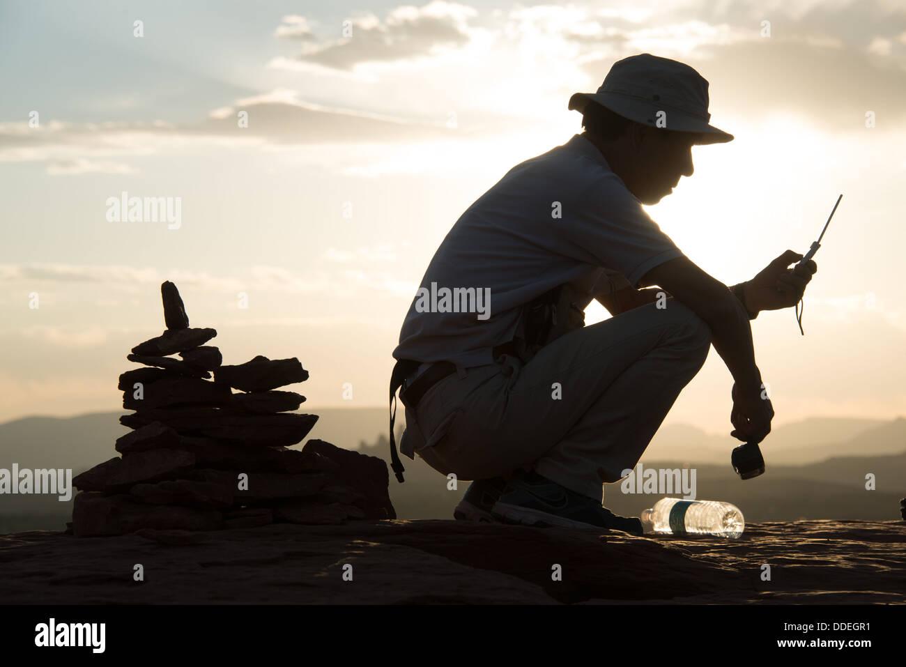 L'uomo Texting con Cairn dietro Aeroporto Vortex Sedona in Arizona Immagini Stock