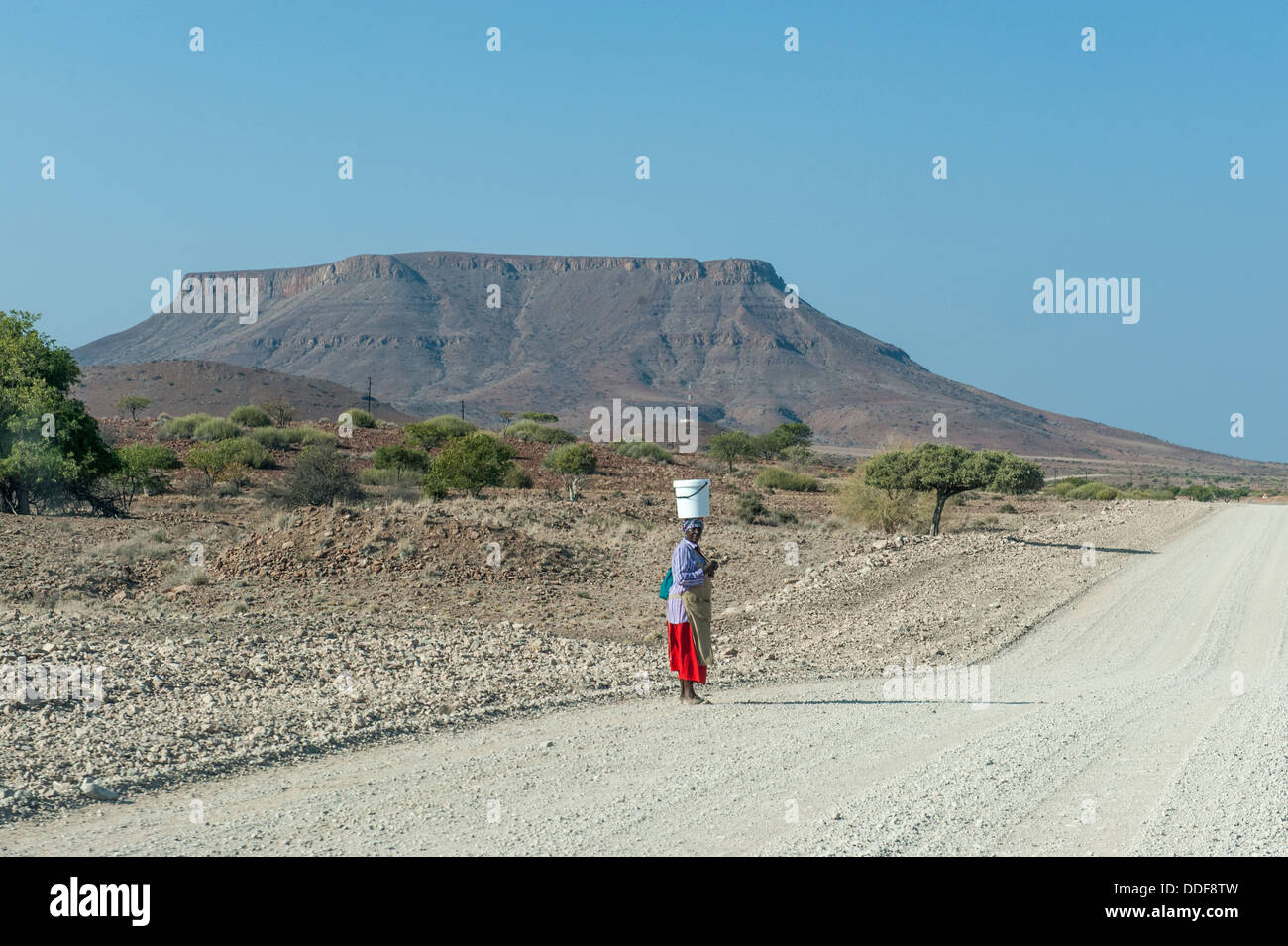 Una donna con un cucchiaio sul suo capo sta in piedi in una strada di ghiaia nel paesaggio secco, Regione di Kunene, Immagini Stock