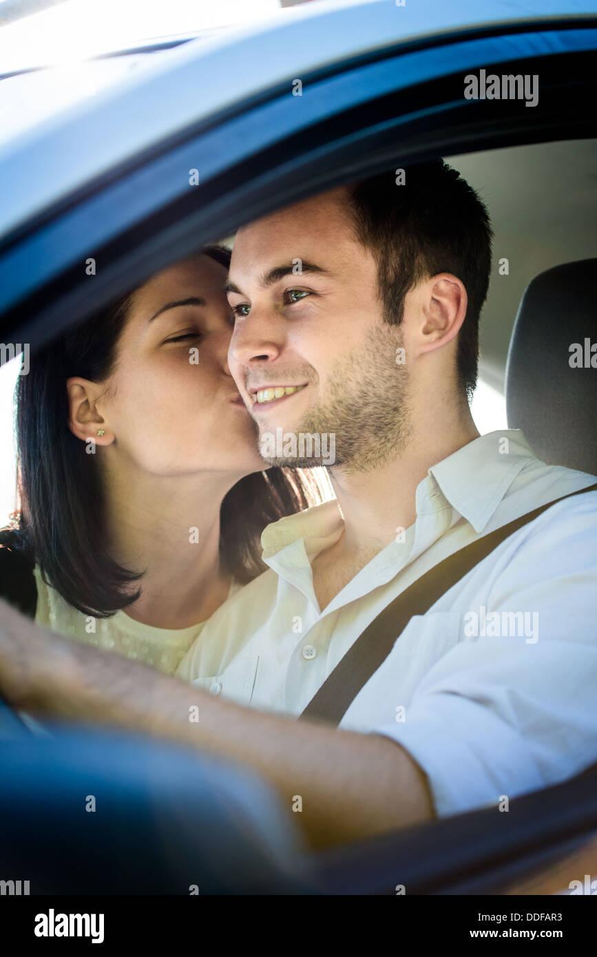 Matura in auto - giovane donna baciare uomo in auto durante la guida Immagini Stock