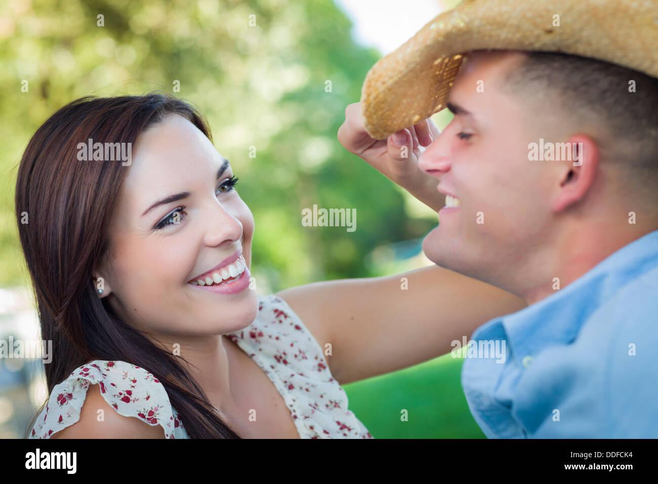 Felice razza mista coppia romantica con il cappello da cowboy flirtare nel parco. Immagini Stock