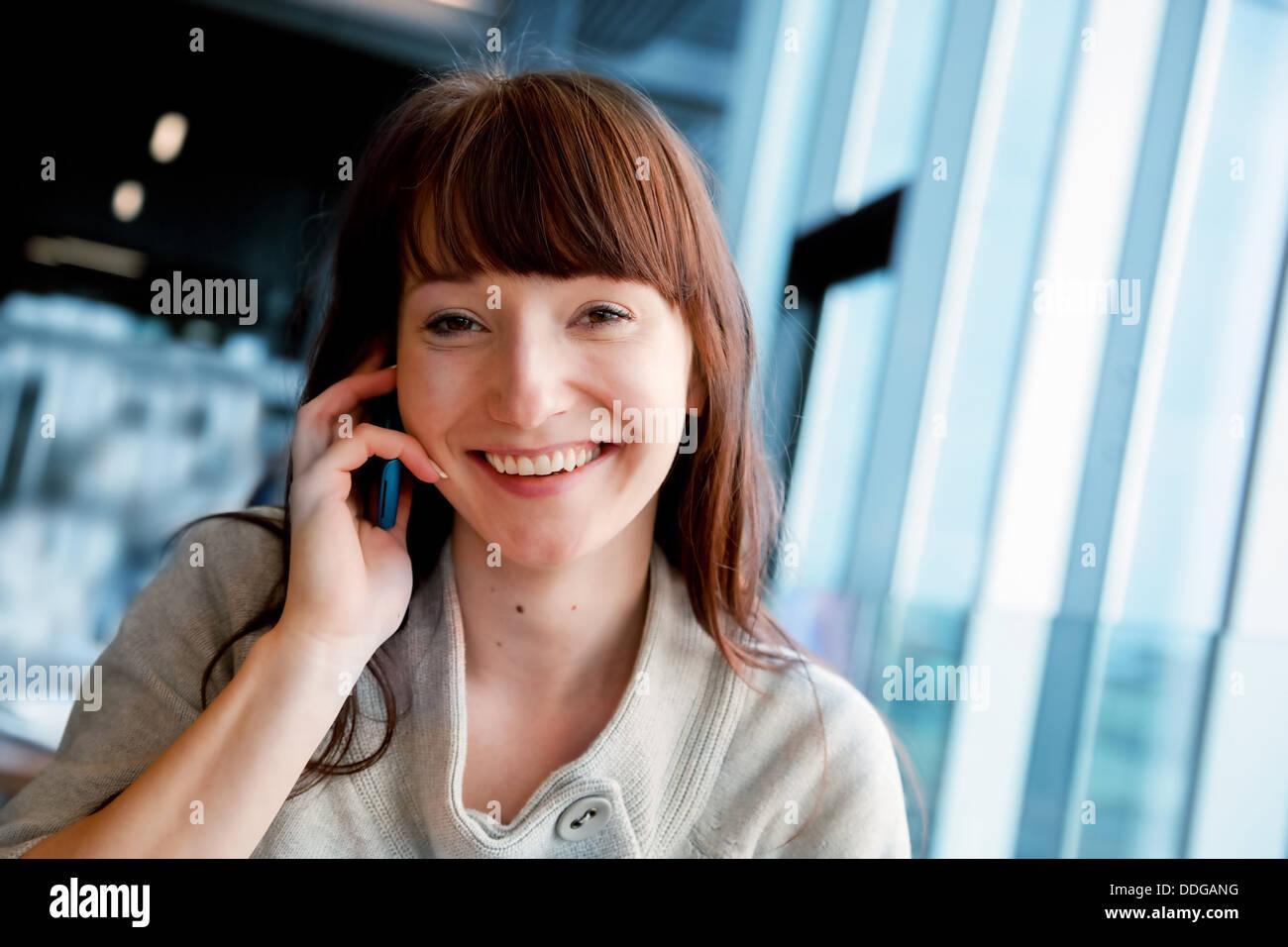 Donna che parla al telefono cellulare e sorridente, guardando la fotocamera Immagini Stock