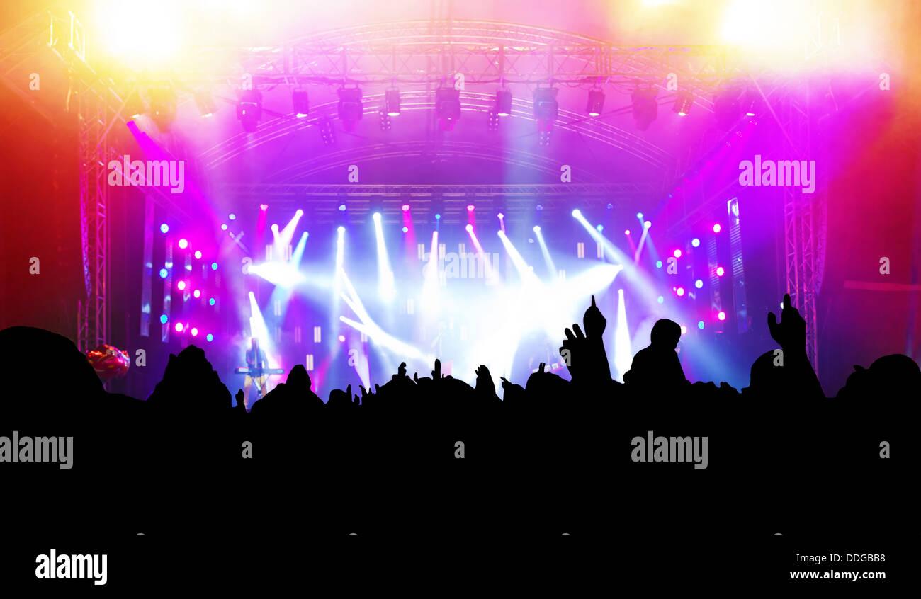 Persone del pubblico con le mani fino avente il divertimento a un concerto di musica / discoteca party. Foto Stock