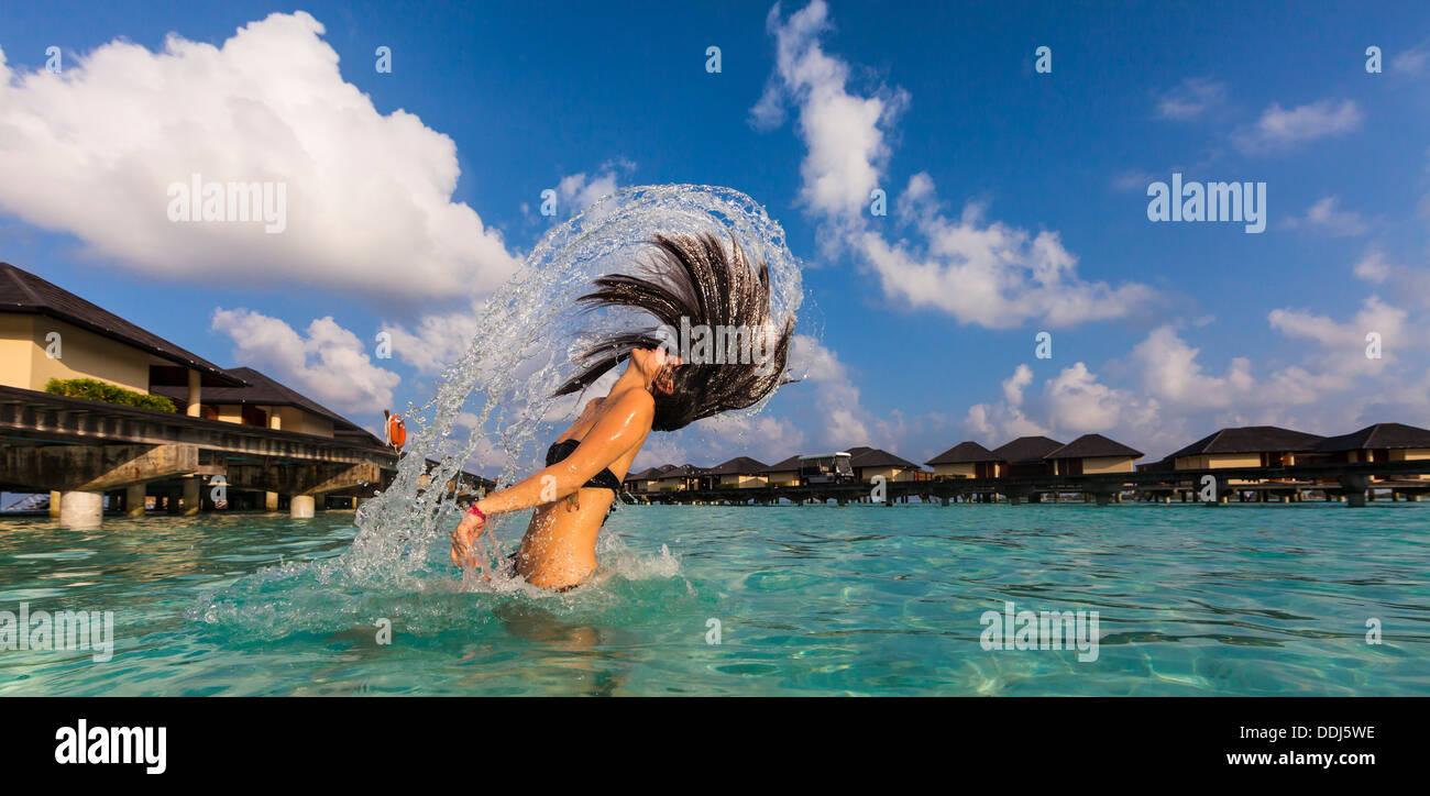 Maldive, giovane donna gli spruzzi di capelli bagnati in laguna Immagini Stock